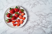 Organic ripe strawberries (whole and sliced) in white ceramic plate on gray marble background, copy space. Healthy food concept, still life. Top view, flat lat