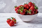 Organic ripe strawberries in white ceramic bowl on gray plaster wall background, copy space. Healthy food concept, still life