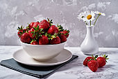 Red organic strawberries in white ceramic bowl on linen table napkin and chamomile flowers in vase on gray concrete background, copy space. Healthy food concept, still life