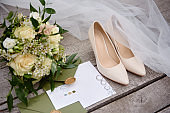 Luxury set of wedding invitations, wedding rings, elegant bride shoes and bridal bouquet on wood brown background. Honeymoon and wedding concept