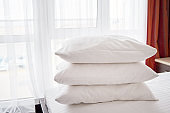 Stack of white soft pillows on comfortable bed sheet with window on background, copy space