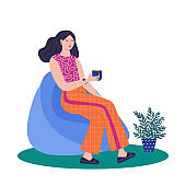 Women sitting in ball chair and resting and drinking coffee.