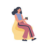 Woman sitting talking, resting and drinking on a comfortable ball chair.