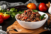 Healthy buckwheat cooked with vegetables in a white bowl on a dark background, a dish of Azerbaijani cuisine, horizontal orientation