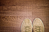 Vintage pair of natural suede sneakers on a wooden floor, top view, with copy space for text. Travel concept.