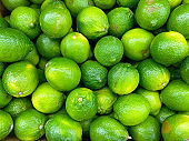 big pile of fresh lemons limes stacked at fruit stand farmers market grocery store