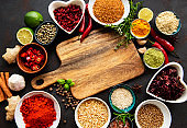 Various spices in a bowls and empty cutting board on black concrete background. Top view copy space.