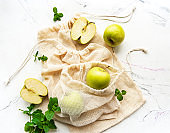 Fresh green apples in a mesh bags, top view.