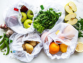 Fruits and summer vegetables in reusable eco friendly mesh bags on marble background. Zero waste shopping. Ecological concept.
