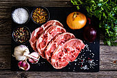 Fresh raw slices of pork neck on wooden table with seasonings and fresh vegetables