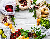 Zero waste shopping and sustanable lifestyle concept, various farm organic vegetables, grains, pasta and fruits in reusable packaging supermarket bags.