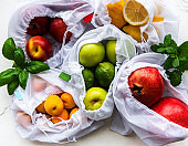 Mesh shopping bags with organic fruits on marble background. Flat lay, top view. Zero waste, plastic free concept.  Summer fruits.