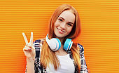 Pretty  woman in wireless headphones listening to music on colorful orange background