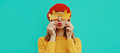 Autumn portrait of beautiful young woman covering her eyes with yellow maple leaves blowing her lips wearing a knitted sweater, red beret on blue background