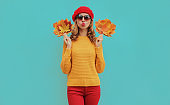 Autumn portrait of beautiful young woman with yellow maple leaves blowing her lips wearing a knitted sweater, red beret on blue background