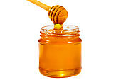 Glass jar of honey with a wooden ladle isolated on white. Organic honey, healthy food, close-up
