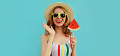 Summer portrait of happy smiling young woman with lollipop or ice cream shaped slice of watermelon wearing a straw hat on a blue background