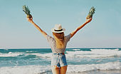 Rear view happy young woman raising her hands up with pineapple on the beach over sea background at summer day