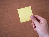 Hand holding blank yellow adhesive note