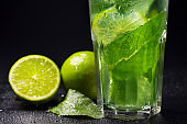 Mojito refreshing cocktail with mint leaves, lime and ice on a black background. Close-up. Soft drink.