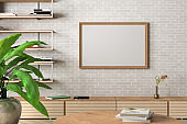 Horizontal blank poster mock up on white brick wall in interior of contemporary living room.