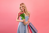 International Women Day sales. Pretty young lady with bouquet of tulips and shopping bags over pink studio background