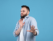 Repulsed millennial guy rejecting something, making STOP gesture over blue studio background