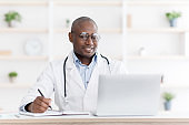 Professional help concept. Friendly black male doctor in white unifrom sitting at table with laptop at his office