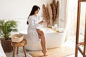 Attractive Woman Applying Moisturizer Cream Caring For Skin In Bathroom