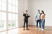 Male Realtor In Medical Mask Showing Buyers New Apartment