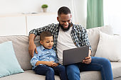 Black Daddy And Son Watching Movie On Laptop At Home