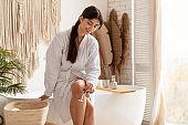 Happy Lady Shaving Legs Removing Hair Sitting In Modern Bathroom