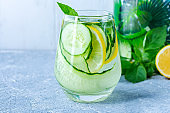 Fresh cool detox water drink with cucumber and lemon. Two glass of Lemonade with mint. Concept of proper nutrition and healthy eating. Fitness diet. Copy space for text.