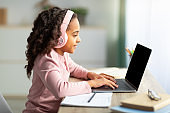 Cute african american girl teenager having online lesson, using laptop and headphones, sitting at desk, side view