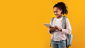 Black girl standing with tablet at yellow studio wall, panorama