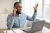 Displeased African Businessman Talking On Cellphone At Workplace In Office