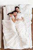 Couple Hugging Sleeping Together Lying In Bedroom, Top View, Vertical