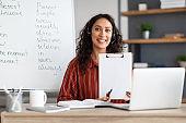 Female teacher in headphones sitting at desk shower paper document