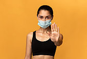 Woman wearing protective face mask showing stop sign gesture
