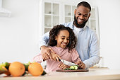 Cheerful african father teaching daughter how to prepare salad