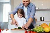 Father And Daughter Cooking Salad Cutting Vegetables Together In Kitchen