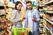 Young couple with cart and smartphone shopping in supermarket