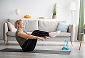 Athletic senior woman doing abs exercises, sitting in boat yoga pose at home, free space