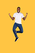 Excited African Man Jumping Shaking Fists Celebrating Success, Yellow Background