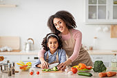 Cheerful black mom teaching daughter how to prepare salad