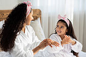 Beautiful mother and daughter applying cream on hands