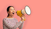 Announcement. Young Asian Lady With Megaphone In Hands Shouting At Copy Space