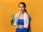 Confident sporty young woman holding water bottle at studio