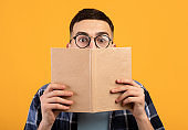 Shocked young guy in glasses hiding behind book, having problem studying for college exams on orange background