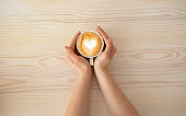 Woman holding cup of coffee latte, with heart shape, enjoying hot beverage in cafeteria, top view